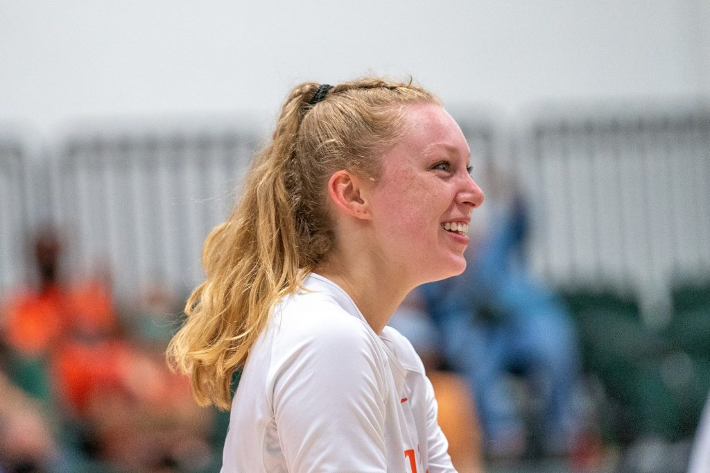 Junior setter Savannah Vach smiles and heads over to celebrate with teammates after the Canes scored a point during their match versus the University of Maryland, Baltimore College on Aug. 29, 2021.