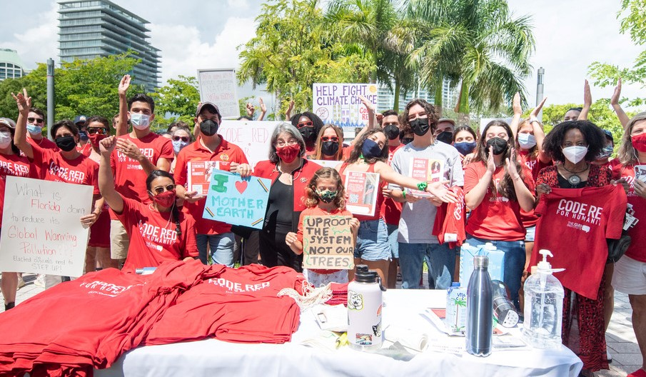 Miami-Dade County Mayor Daniella Levine Cava and a group of UM students hold signs protesting budget cuts to the climate department of the City of Miami government on Sept. 13. Dozens of students attended the budget hearing to advocate for increased funding for climate control efforts.