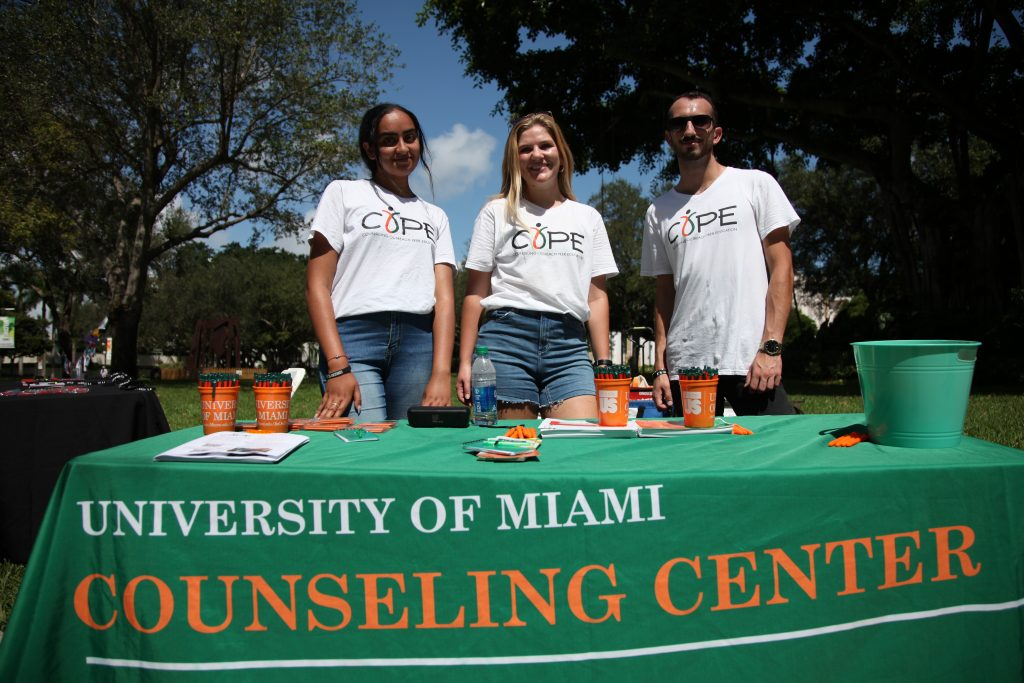 Leaders of UM's Counseling Outreach Peer Organization, or COPE, stand at a table in the middle of UM's Coral Gables campus during an event Wednesday, Oct. 6.