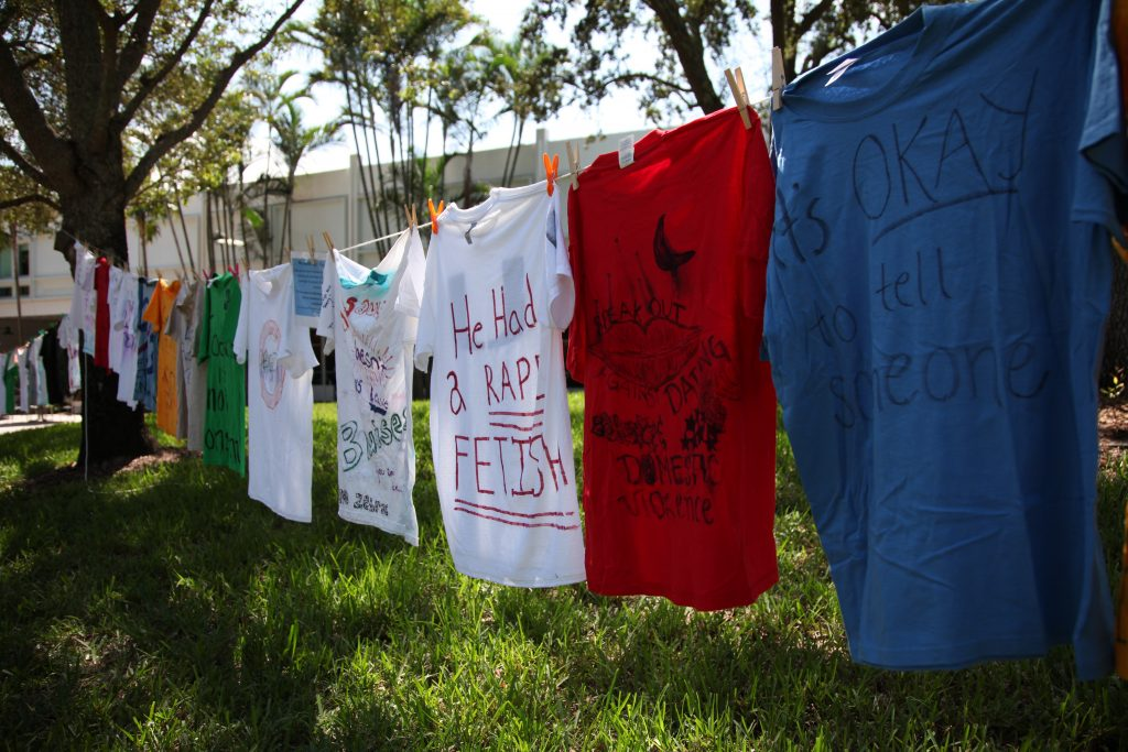 Shirts with various messages related to gender-based violence line the walkway next to 'The U' statue on UM's Coral Gables campus Wednesday, Oct. 6.