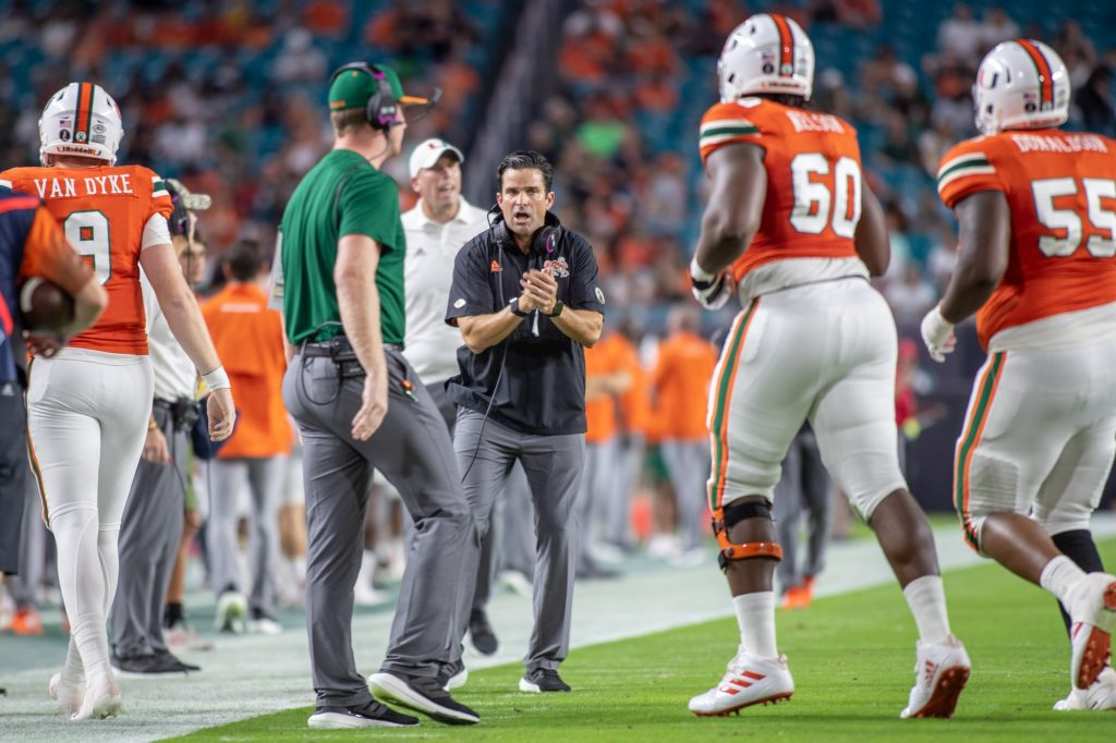 Head coach Manny Diaz encourages players as they leave the field after an offensive drive. Miami lost to Virginia 30-28 after a missed field goal attempt in the final seconds of the game at Hard Rock Stadium on Thursday Sept. 30.