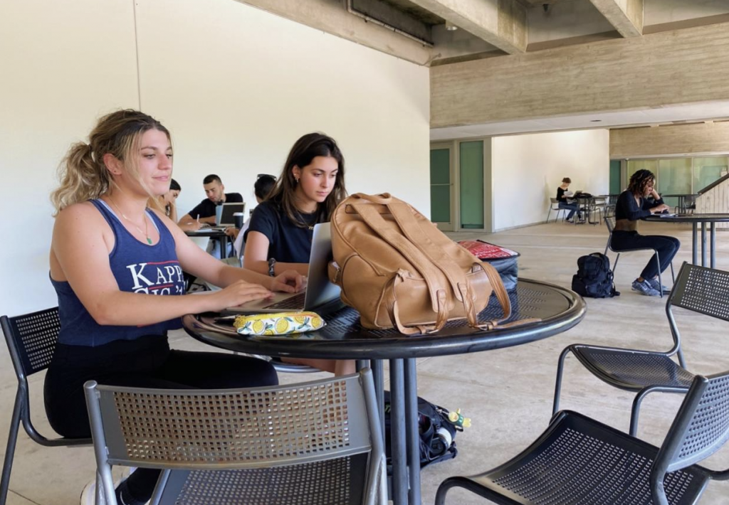 Students outside the Cox Science Building auditorium work on their laptops Tuesday, Sept. 27. University of Miami Information Technology recently added more wireless access points to that area.