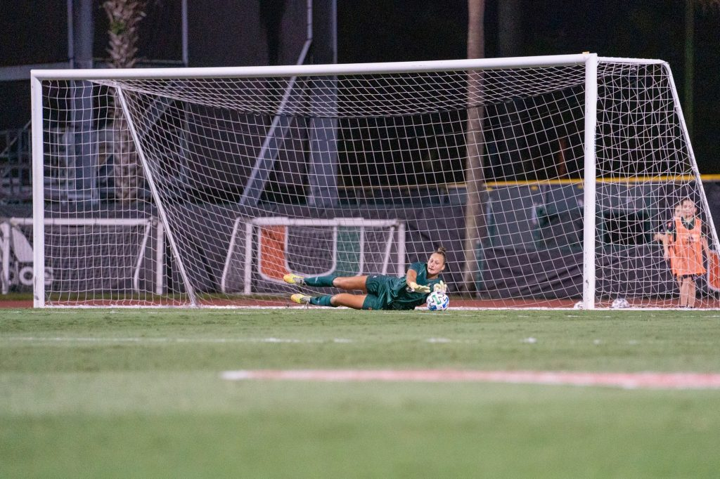 Junior goalkeeper Melissa Dagenais dives to make a save during the first half of Miami's match versus Clemson at Cobb Stadium on Oct. 16, 2021. Dagenais had 7 saves in the Canes' 0-1 loss.