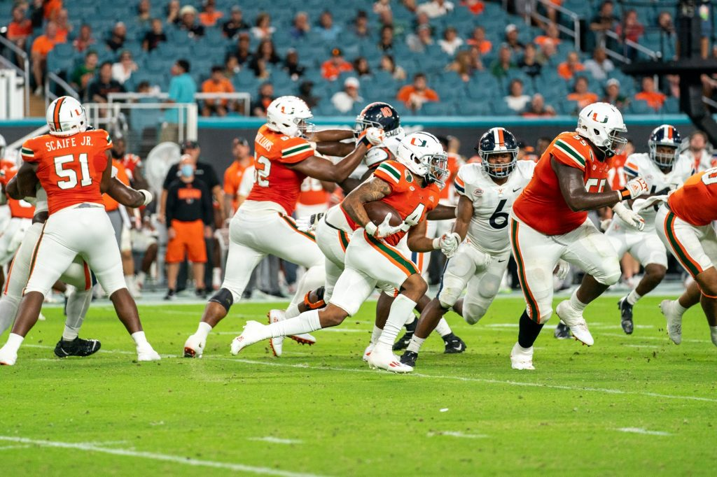 Freshman running back Jaylan Knighton rushes downfield with the ball during the third quarter of Miami's game versus the University of Virginia at Hard Rock Stadium on Sept. 30, 2021. Knighton had 15 carries, totaling 44 yards.