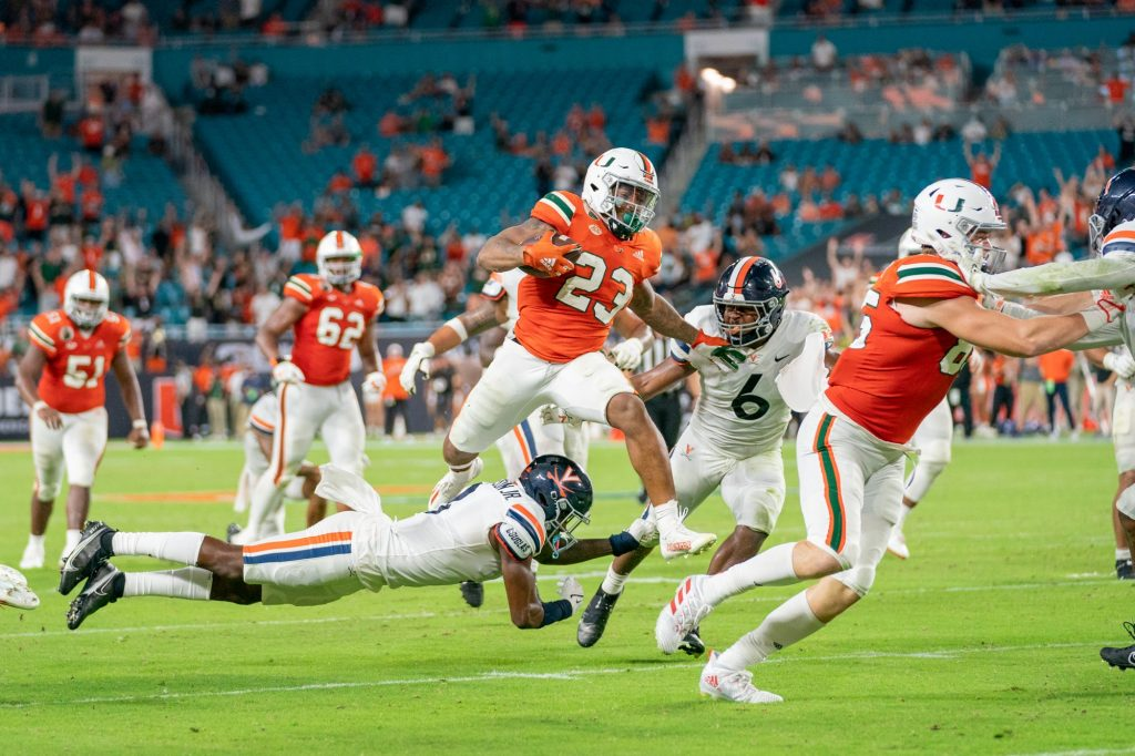 Junior running back Cam'Ron Harris leaps over a Virginia defender during the fourth quarter of Miami's game versus the University of Virginia at Hard Rock Stadium on Sept. 30, 2021. Harris had 14 carries for 111 yards and two touchdowns.