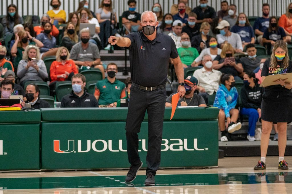 """Head coach Jose """"Keno"""" Gandara points something out to his players during the first set of Miami's match versus the University of North Carolina  in the Knight Sports Complex on Oct. 1, 2021."""