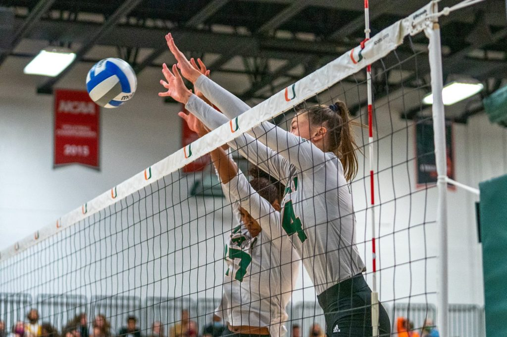 Redshirt sophomore outside hitter Angela Grieve and junior middle blocker Janice Leao reach up to block a shot in the third set of Miami's match versus the University of North Carolina in the Knight Sports Complex on Oct. 1, 2021.